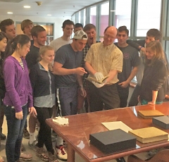"Professor Wilkin holding the first edition of Galileo's 1610 book announcing the discovery of 4 moons around Jupiter. The students are from the Sophomore Research Seminar ""New Worlds""."