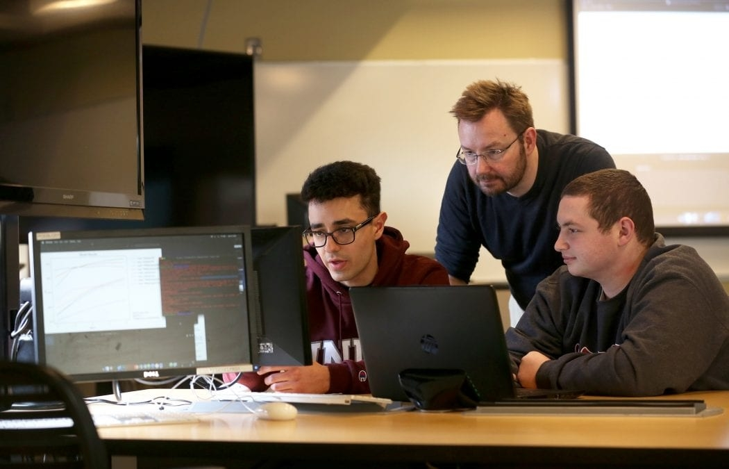 Students working on a data analytics project with Nick Webb