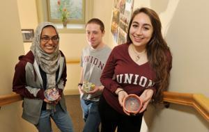 Empty Bowls student organizers Sharmeen Azher '17, Ian Koon '18 and Hannah Ellen '19 hold bowls that will be available at this weekend's event. (Paul Buckowski/Times Union photo)