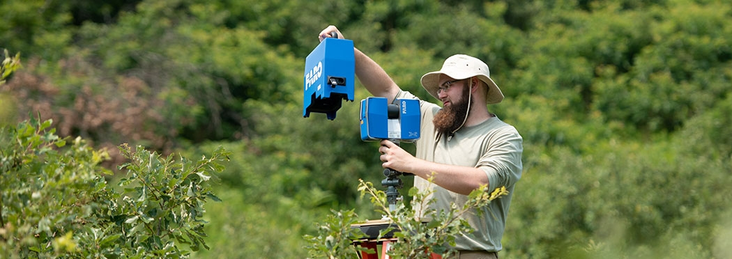 Sean Rigney '20 uses a terrestrial laser scanner to collect 3D images of the shrub structure in the Albany Pine Bush Preserve. Working with Steve Rice, professor of biology,