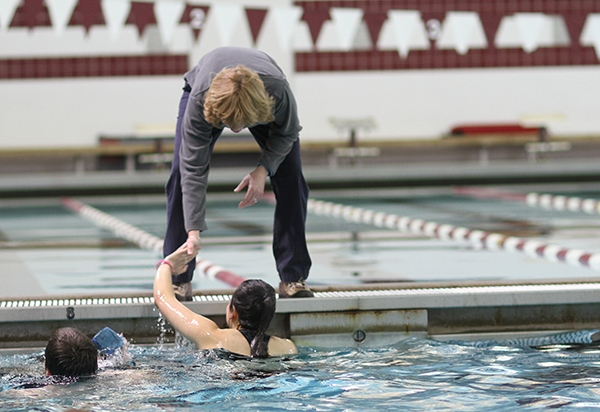 Trainer Cheryl Rockwood high fives a student in the pool.