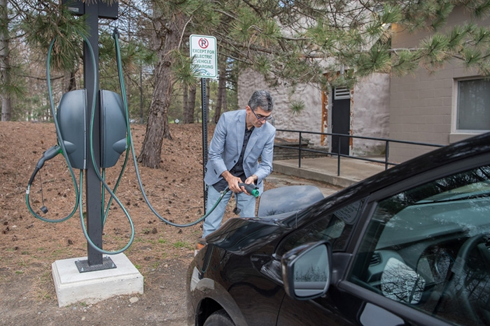 Daniel Mosquera charges his electric vehicle on campus on a recent morning.