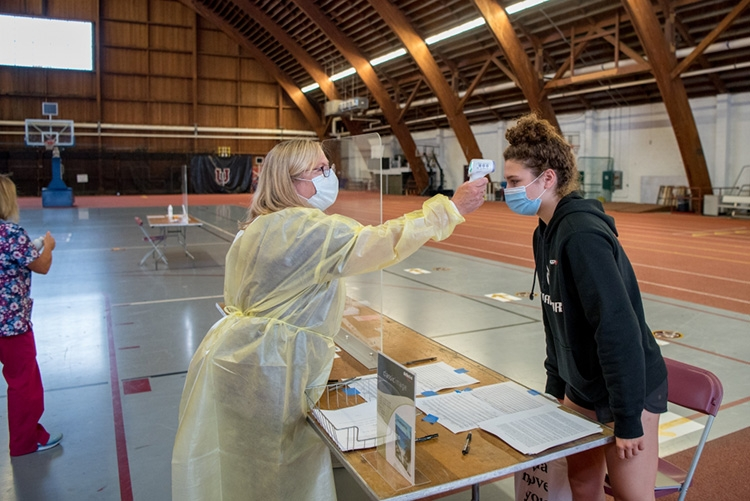 Celeste Beaudoin '24 has her temperature checked by registered nurse Joan Thompson in the COVID-19 testing site in Memorial Field House.
