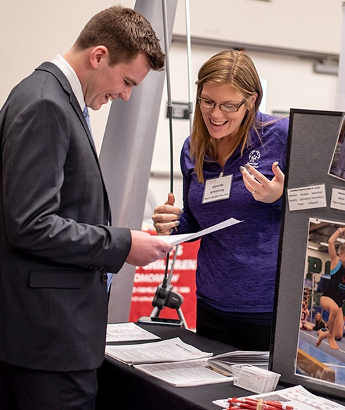 A Union student speaks with a prospective employer at the Becker Career Fair