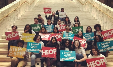 Students and staff with signs sitting on the stairs at the State Capitol in Albany