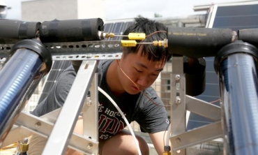 Sunan Sun '20 works on the roof of Wold Center as part of his research learning about the applications of solar energy.