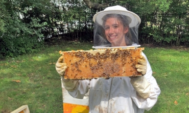 Gabriela Basil '22, a member of Union's Beekeeping Club, inspects a hive.