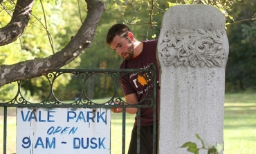 A student volunteer painting a fence in Vale Park, Schenectady