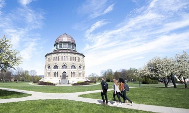 Students walking across campus with the Nott Memorial in the background