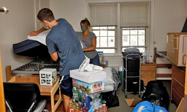 A student moving into a dorm room on campus